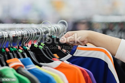 Fashion beautiful clothes hang on a shelf on blurred background