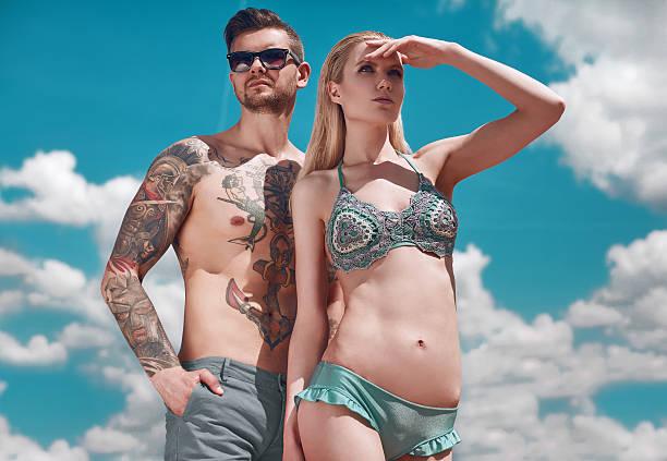 fashion beautiful couple getting a suntan - ehepaar tattoos stock-fotos und bilder