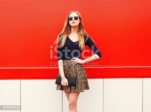istock Fashion beautiful woman in leopard skirt sunglasses handbag clutch posing 579764010