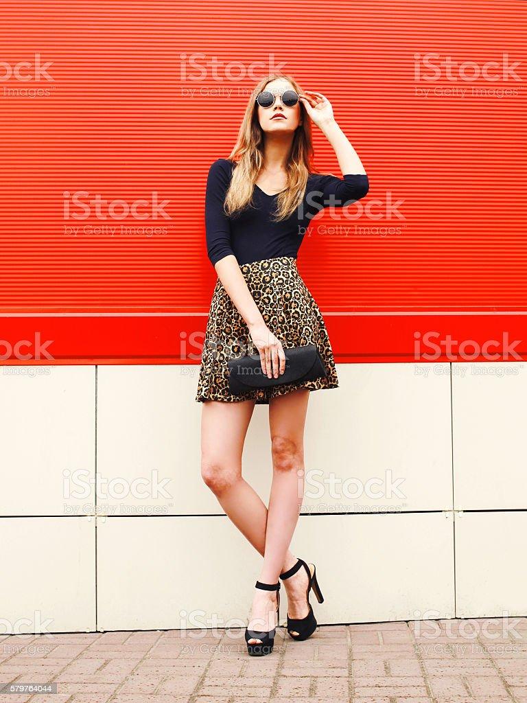 Cтоковое фото Fashion beautiful woman in leopard skirt sunglasses handbag clutch posing