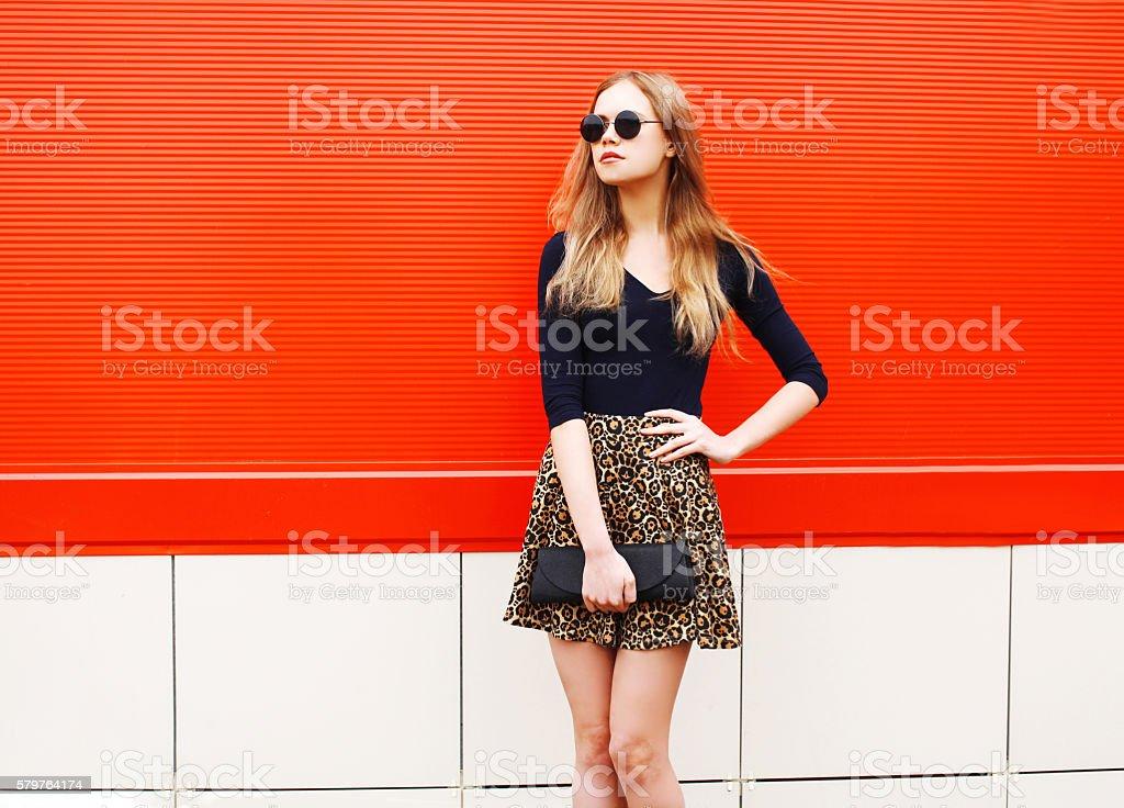 Fashion beautiful woman in leopard skirt sunglasses handbag clutch posing stock photo