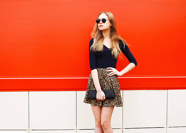 fashion beautiful woman in leopard skirt sunglasses handbag clutch posing - rock tiere stock-fotos und bilder