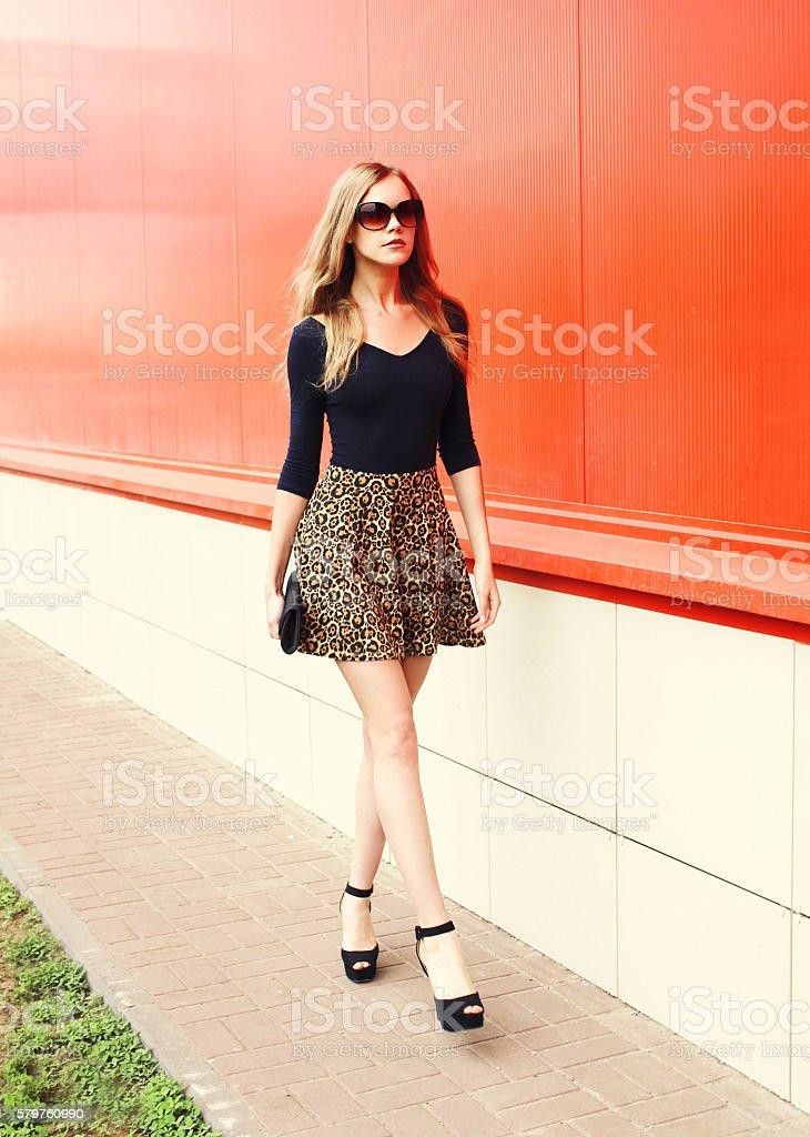 Cтоковое фото Fashion beautiful young woman in leopard skirt sunglasses handbag clutch
