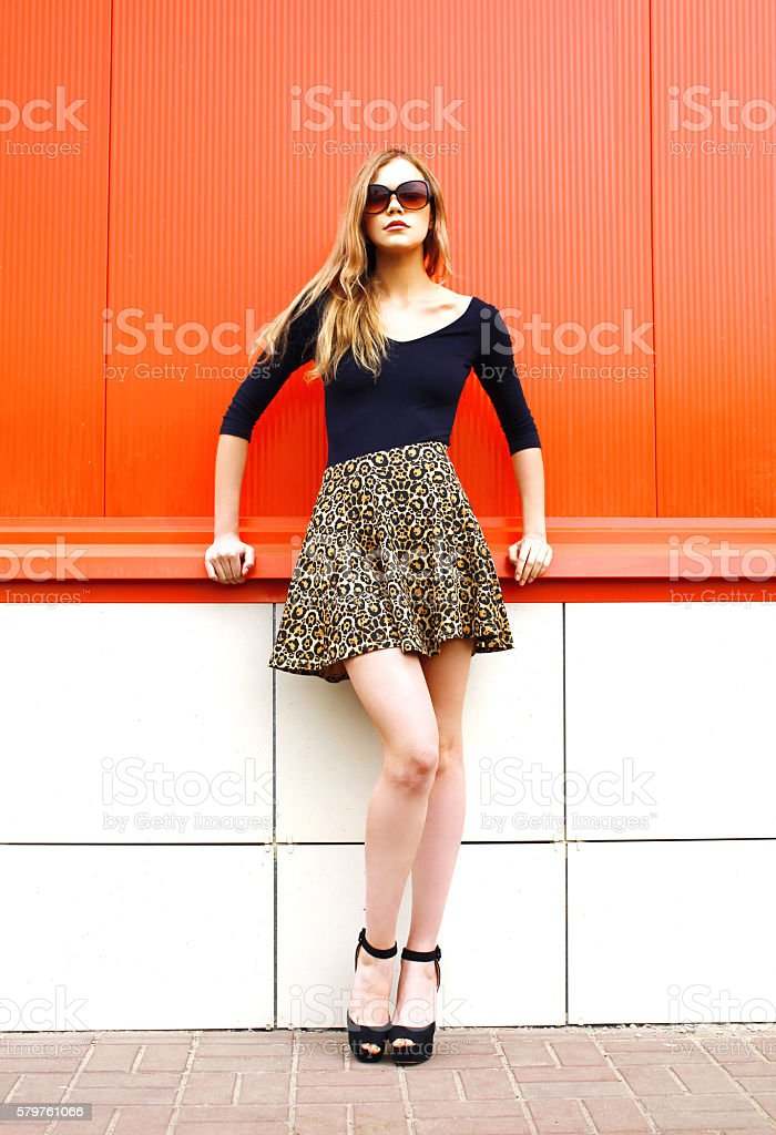Fashion beautiful young woman in leopard skirt sunglasses over red стоковое фото