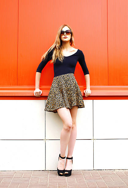 Fashion beautiful young woman in leopard skirt sunglasses over red – zdjęcie