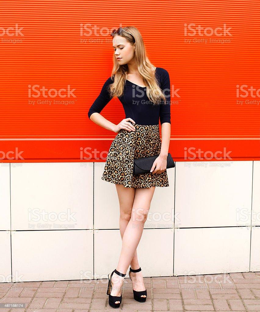 Moda hermosa joven mujer en falda con handbag clut leopardo - foto de stock