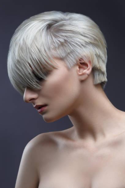 mode schönheit porträt ein blondes mädchen mit einem stylischen kurzhaarschnitt, pony schließt die augen. - kurzhaarfrisuren mit pony stock-fotos und bilder