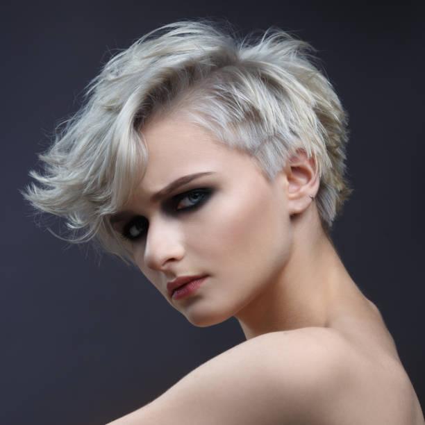 mode schönheit porträt ein blondes mädchen mit einem stylischen kurzhaarschnitt auf grauem hintergrund. - kurzhaarfrisuren mit pony stock-fotos und bilder