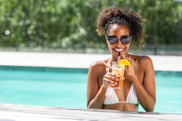 Fashion beauty woman in pool drinking cocktail Portrait of happy fashion woman with sunglasses standing in swimming pool drinking cocktail. Beautiful african glamour girl with fresh soft drink for appetizer in luxury pool looking at camera. Young woman with shades holding tumbler cocktail enjoying summer vacation. poolside stock pictures, royalty-free photos & images