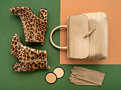Top view on a pair of trendy leopard print boots, crocodile crossbody bag, leather gloves, and makeup products. Flat lay of feminine trendy accessories in green and beige tones.