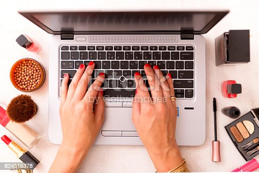 istock Fashion blogger working at office desk with a laptop: fashion, beauty and technology concept 824316378