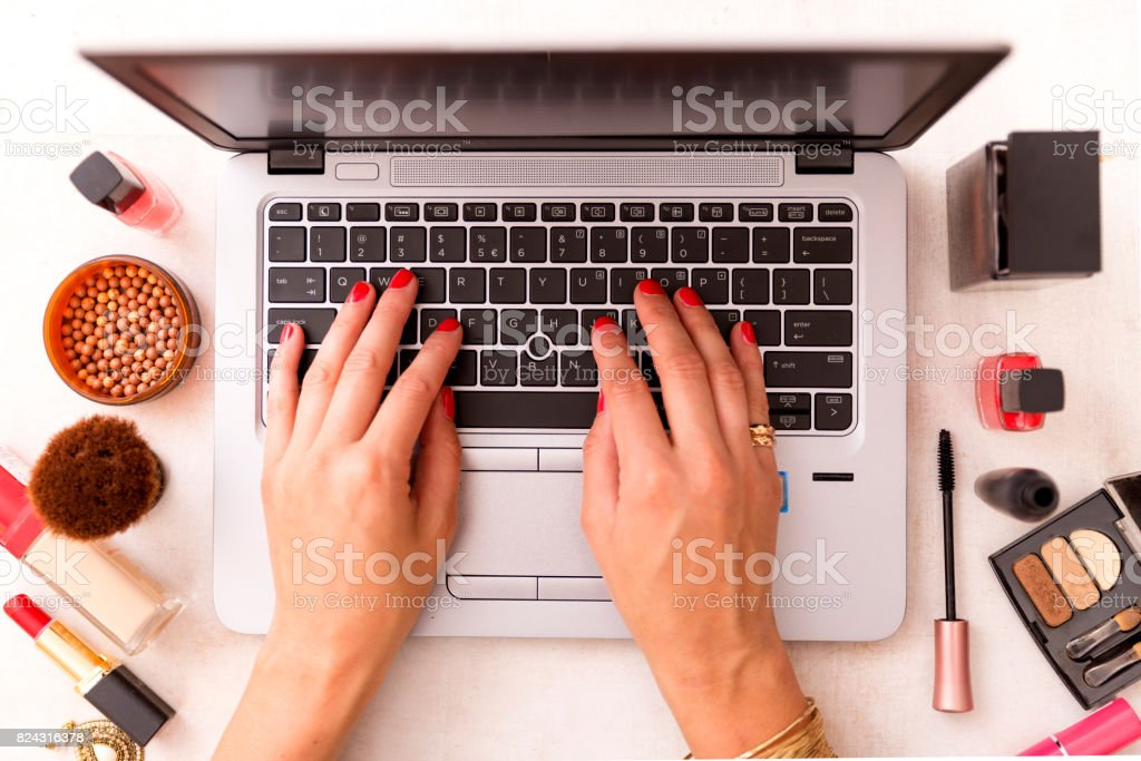 Fashion blogger working at office desk with a laptop: fashion, beauty and technology concept stock photo