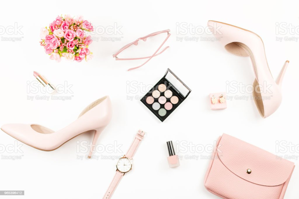 Fashion blogger workspace flat lay with pumps, cosmetics, purse, planner book and flowers. royalty-free stock photo