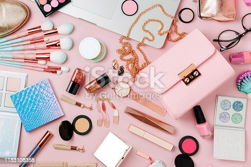 istock Fashion blogger workspace with laptop and female accessory, cosmetics products on pale pink table. flat lay, top view 1153108358