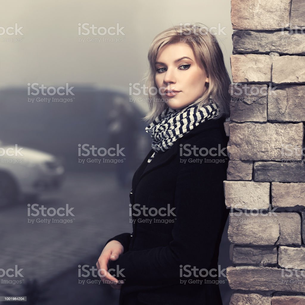 Fashion blond woman in black coat leaning on wall in city street stock photo