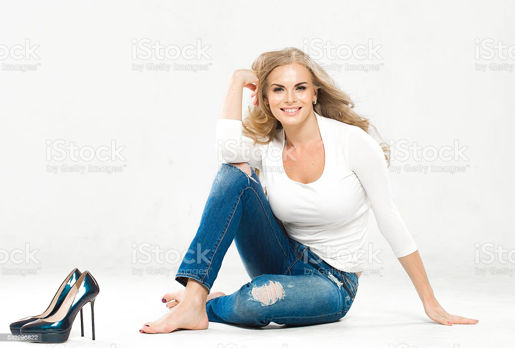 Fashion blond woman in jeans sitting on floor stock photo