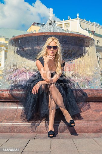 Fashion Blonde Girl Sitting on Bench Near Fountain. Street Fashion. Urban Lifestyle. Young Beautiful Woman Walking Outdoor.