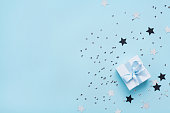 istock Fashion blue background with gift or present box, stars and sequins top view. Flat lay. Greeting card for birthday or christmas. 869355744