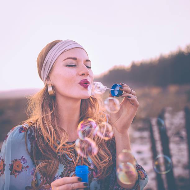 mode boho-mädchen blasen blasen in der natur - hippie kleider stock-fotos und bilder