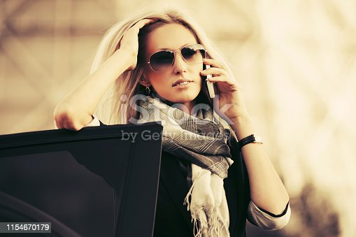 Fashion blonde business woman talking on cell phone outside a car Stylish female model wearing sunglasses and scarf