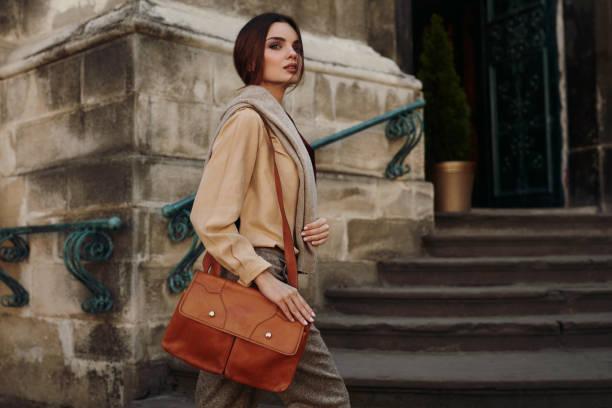 modischer kleidung. schöne frau in modische outdoor-bekleidung - leder handtaschen damen stock-fotos und bilder
