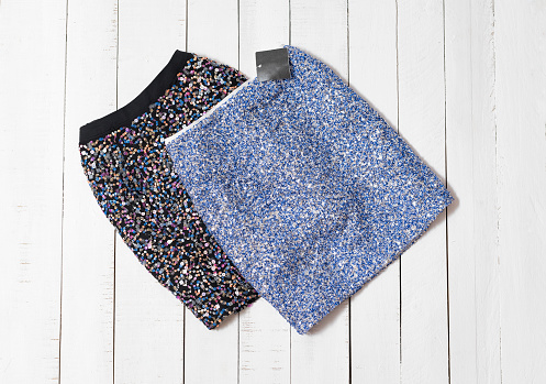 Fashion clothes. Black and blue sparkle mini skirts on white wooden floor planks