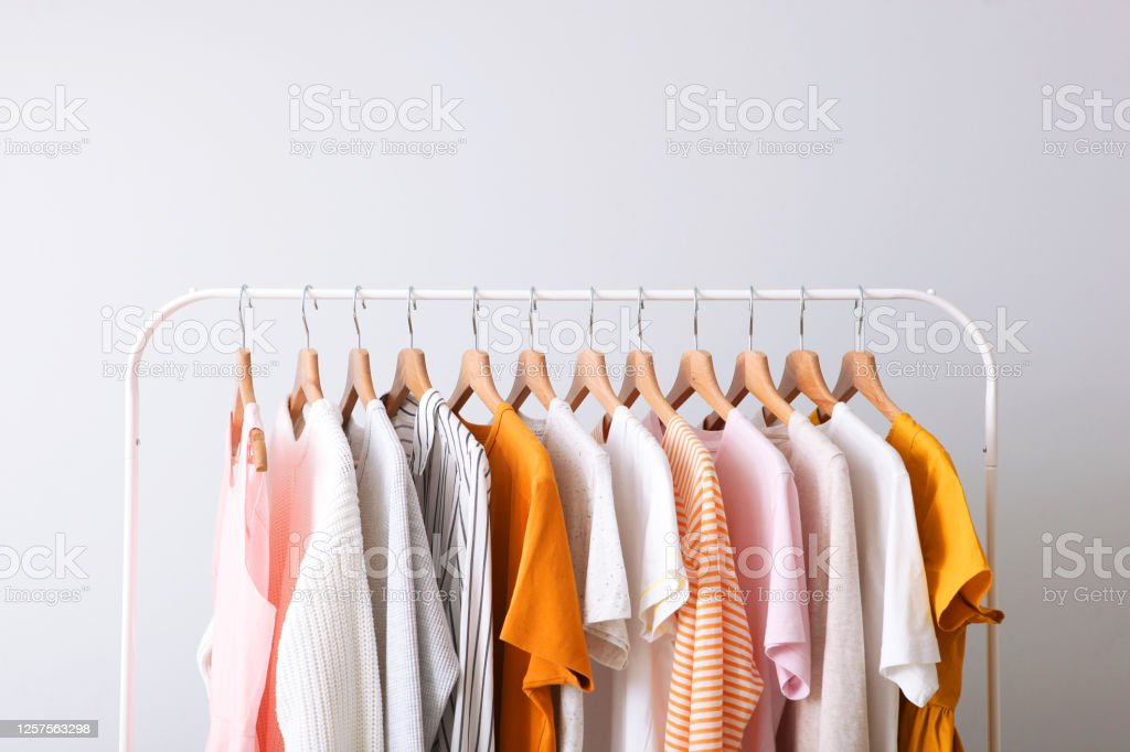 fashion clothes on a rack in a light background indoors. place for text fashion clothes on a rack in a light background indoors. place for text Clothing Stock Photo