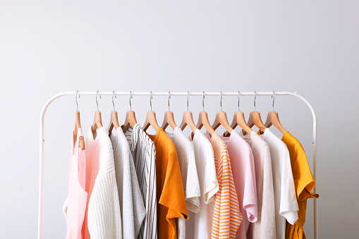 fashion clothes on a rack in a light background indoors. place for text