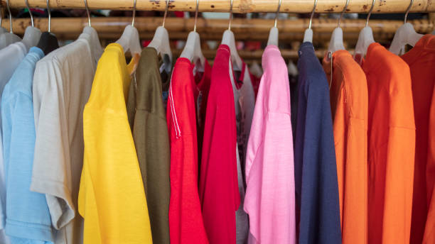 Fashion clothes on clothing rack - bright colorful closet. Closeup of rainbow color choice of trendy female wear on hangers in store closet or spring cleaning concept. Summer home wardrobe stock photo