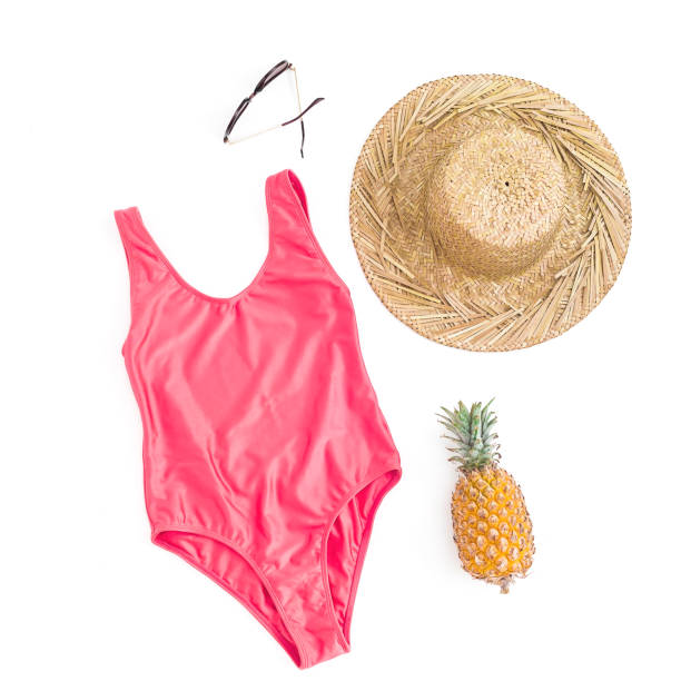 Fashion composition of pineapple fruit, sun glasses, straw hat and pink bikini swimwear on white background. Flat lay, top view Fashion composition of pineapple fruit, sun glasses, straw hat and pink bikini swimwear on white background. Flat lay, top view swimwear stock pictures, royalty-free photos & images