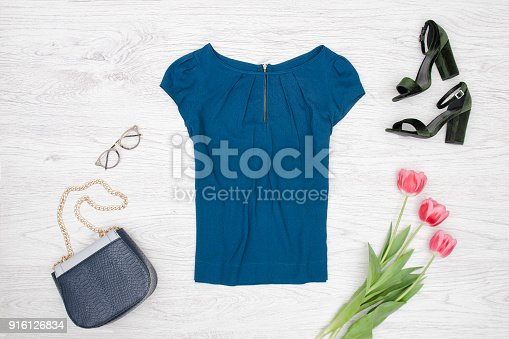 istock Fashion concept. Blue blouse, handbag, glasses, black shoes and pink tulips. Top view 916126834
