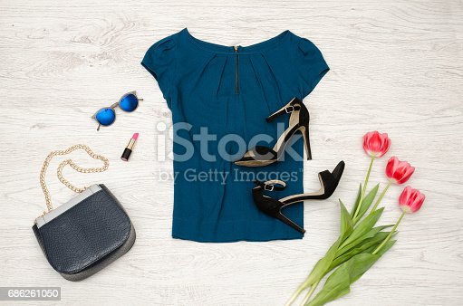 istock Fashion concept. Blue blouse, handbag, round glasses, lipstick, black shoes and pink tulips. Top view, light wood background 686261050