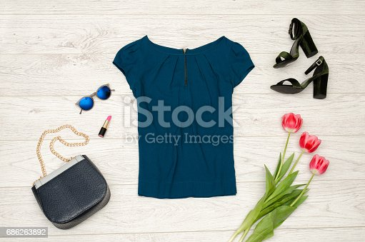 istock Fashion concept. Blue blouse, handbag, round glasses, lipstick, black shoes and pink tulips. Top view, light wood background 686263892