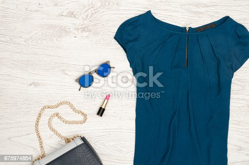 istock Fashion concept. Blue blouse, round glasses, lipstick and part of handbag. Top view 675974854