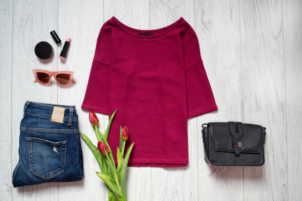 fashion concept. maroon top, tulips, blue jeans, black bag, sunglasses, lipstick. spring wardrobe. wooden background. - spring fashion stock pictures, royalty-free photos & images