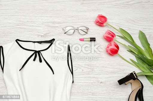 istock Fashion concept. Part of a white blouse, glasses, lipstick and pink tulips. Top view 675974844
