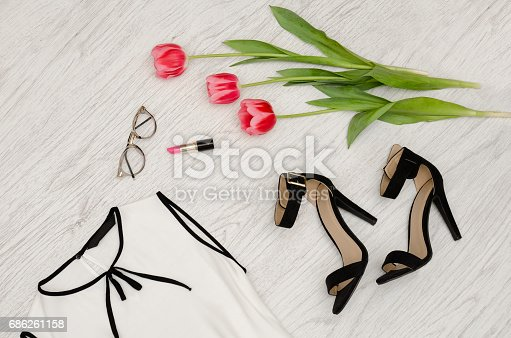istock Fashion concept. Part of a white blouse, glasses, lipstick and pink tulips. Top view, close up 686261158