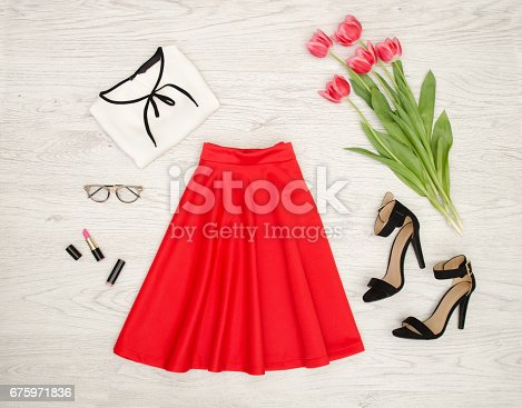 istock Fashion concept. Red skirt, blouse, sunglasses, lipstick, black shoes and pink tulips. 675971836