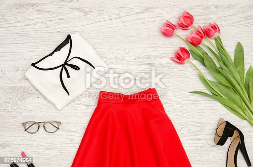 istock Fashion concept. Red skirt, blouse, sunglasses, lipstick, black shoes and pink tulips. 675974964