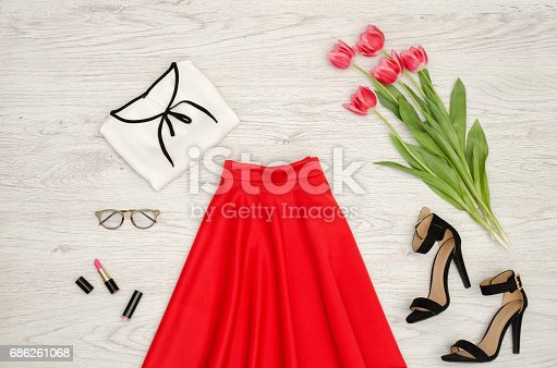 istock Fashion concept. Red skirt, blouse, sunglasses, lipstick, black shoes and pink tulips. Top view, light wood background 686261068