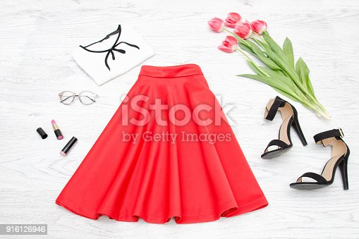 istock Fashion concept. Red skirt, blouse, sunglasses, lipstick, black shoes and pink tulips. Top view 916126946