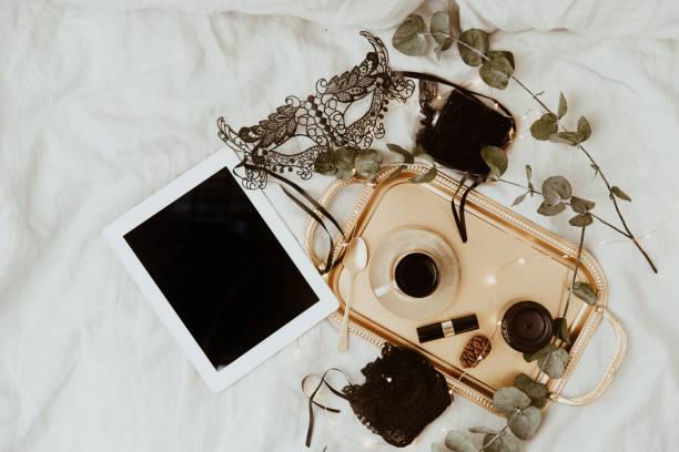 modekonzept. satz von schwarze maske, glamourösen stilvollen sexy dessous, frau zubehör auf gold tablett über bett - bett landhausstil stock-fotos und bilder