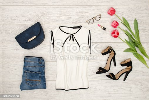 istock Fashion concept. White blouse, blue handbag, glasses, lipstick, black shoes and pink tulips. Top view, light wood background 686263870