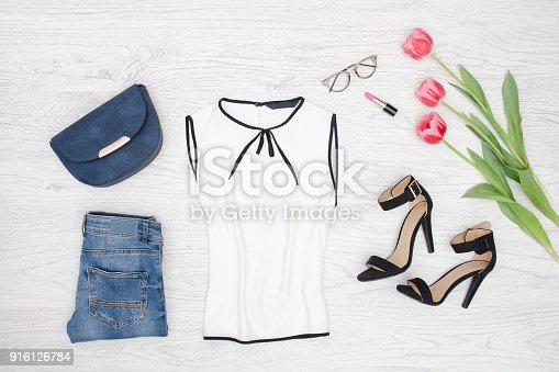 istock Fashion concept. White blouse, glasses, jeans, handbag and pink tulips. Top view 916126784
