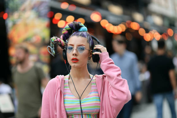 Fashion cool funky girl in headphones listening to music wearing colorful pink sweater and fancy sunglasses on a street with pubs and bars. Unrecognisable incidental people behind stock photo