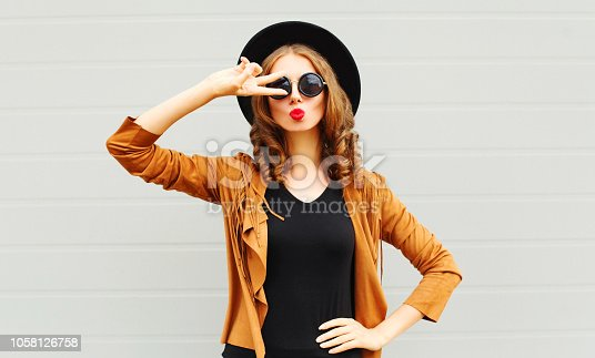 529664088istockphoto Fashion cool girl in black round hat, sunglasses makes air kiss on gray wall background 1058126758