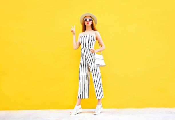 cooles mode-mädchen trägt einen weißen gestreifter hose, runden hut posiert auf bunten gelben hintergrund - kinderhandtaschen stock-fotos und bilder