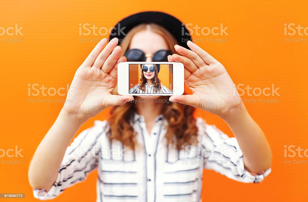 Fashion cool girl taking picture self portrait on smartphone stock photo