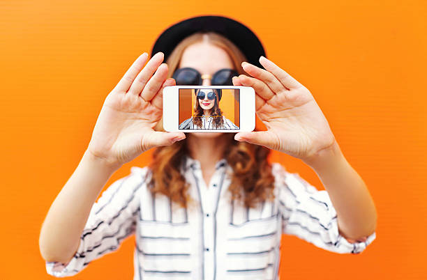 fashion cool girl taking picture self portrait on smartphone - 写真メール ストックフォトと画像