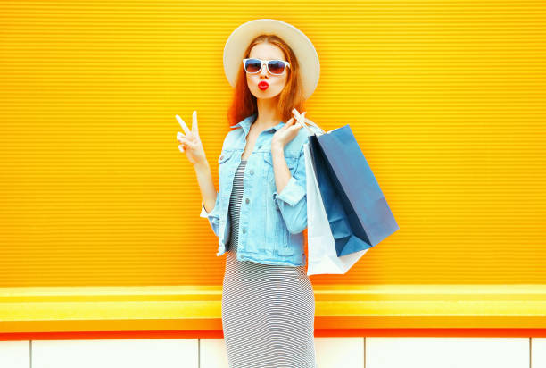 Fashion cool young girl makes an air kiss holds a shopping bags in straw hat on orange background stock photo